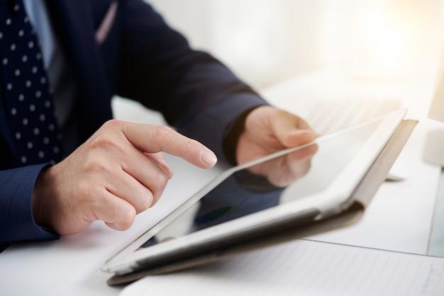 Mãos de homem irreconhecível em trajes formais usando tablet digital no trabalho