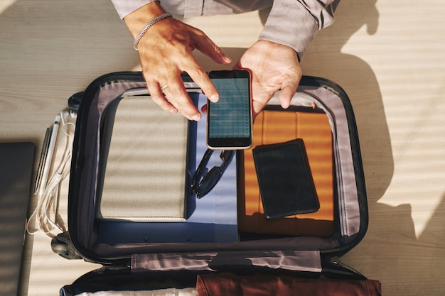 Mãos de homem irreconhecível, embalagem para viagem e verificação de smartphone