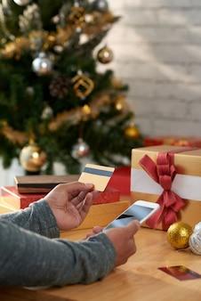 Mãos de homem irreconhecível, segurando o smartphone e cartão de crédito na frente da árvore de natal