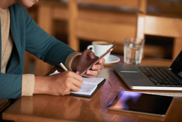Mãos de homem irreconhecível, sentado à mesa no café com gadgets e escrevendo no caderno