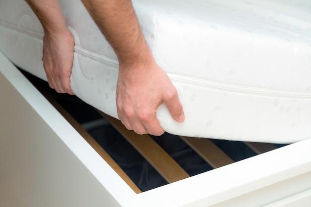 Mãos de homem levantando o colchão no quarto. olhando para a estrutura da cama, inspeciona o colchão