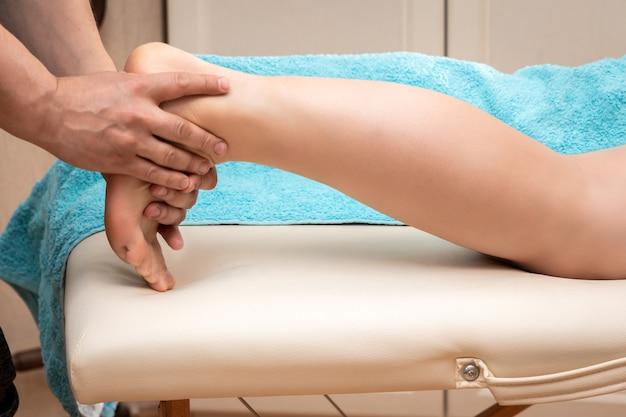 Mãos de homem massagista realizam massagem de pernas e pés para o conceito de mulher, saúde e cuidados com os pés