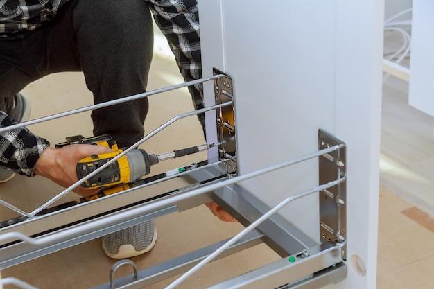 Mãos de homem, montagem de lixeira de móveis na cozinha