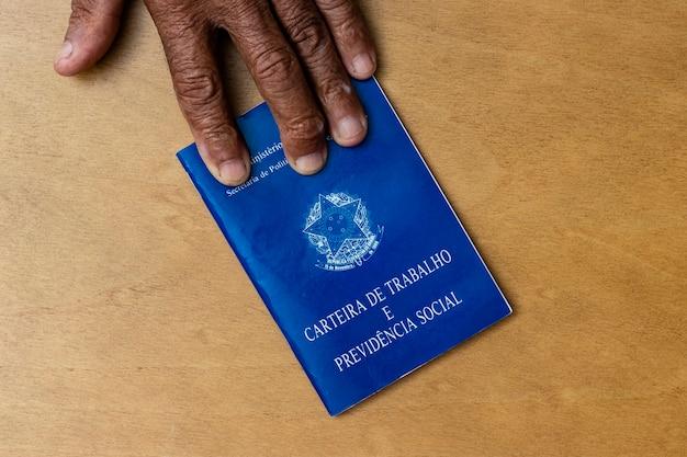 Mãos de homem negro sênior segurando pasta de trabalho, documento da previdência social brasileira
