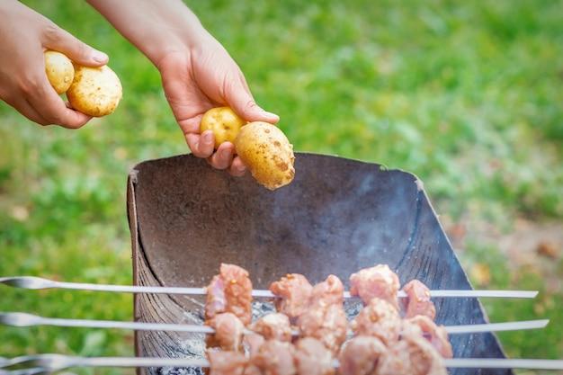 Mãos de homem prepara carne de churrasco com batatas no espeto por grelha em chamas ao ar livre. conceito de preparação de alimentos rústicos de estilo de vida