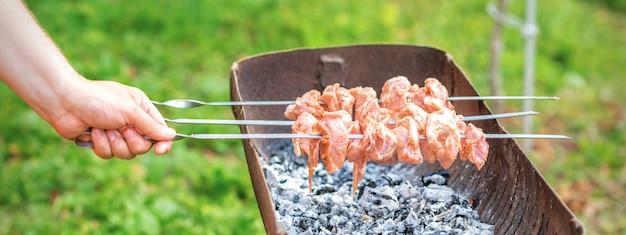Mãos de homem prepara carne de churrasco