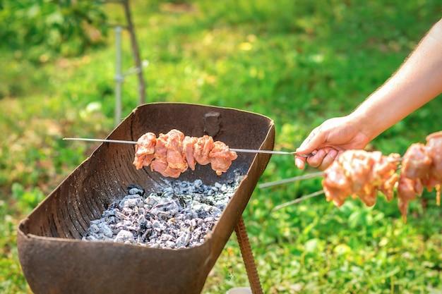 Mãos de homem preparando carne de churrasco