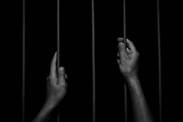 Mãos de homem segurando barras de ferro na prisão. conceito de criminoso preso.