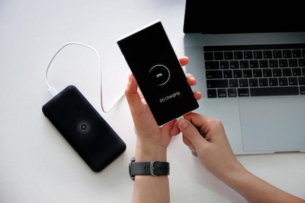 Mãos de homem segurando bateria de carregamento de smartphone de banco de energia externo com o uso de tecnologia de carregamento pd