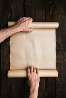 Mãos de homem segurando o rolo de papel estressado em fundo de barwood velho. wanderlust expedição conceito criativo. espaço vazio, espaço para texto, letras. maquete de banner horizontal.