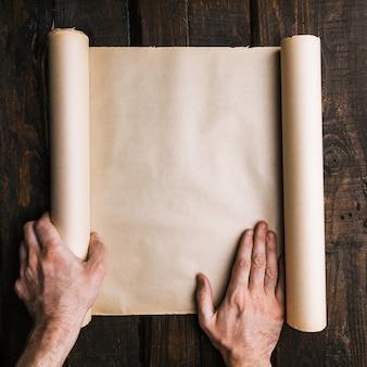 Mãos de homem segurando o rolo de papel marrom velho no fundo escuro de pranchas de madeira. viagem aventura conceito minimalista criativo. procura de tesouro, maquete plana de leigos. espaço para texto, letras, cópia espaço