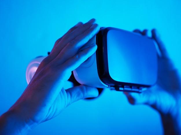 Mãos de homem segurando óculos 3d 360 vr auricular na luz de néon azul roxa futurista.
