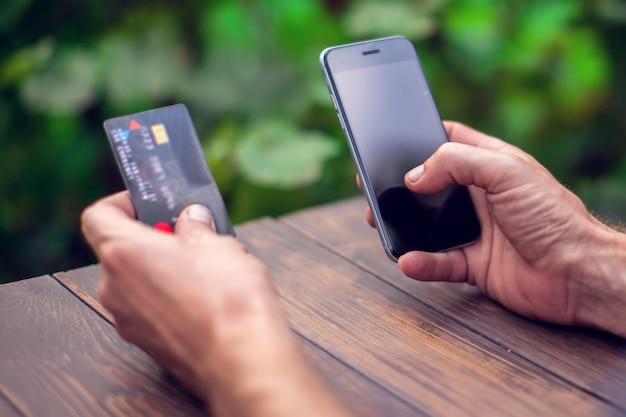 Mãos de homem segurando um cartão de crédito e usando telefone inteligente para pagamento on-line