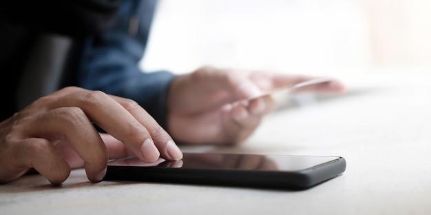 Mãos de homem segurando um cartão de crédito e usando um smartphone para fazer compras online