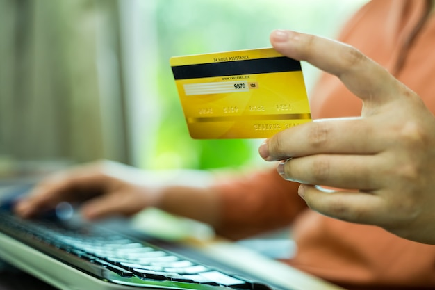 Mãos de homem segurando um cartão de crédito