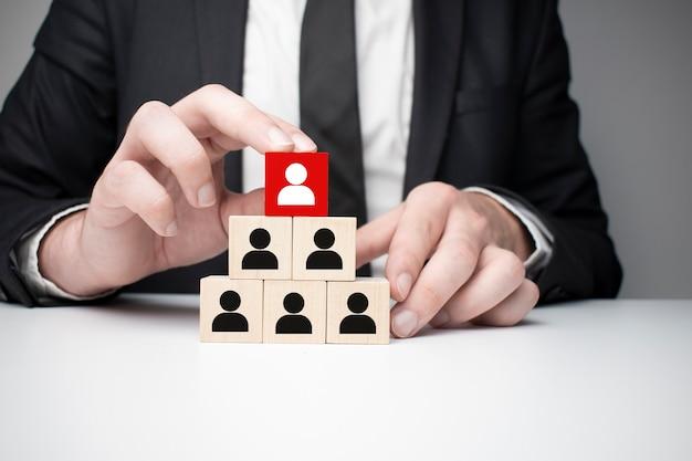 Mãos de homem segurando um cubo com muitos símbolo humano, liderança e conceito de hierarquia corporativa, espaço de cópia.