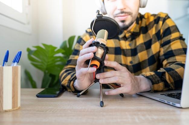 Mãos de homem segurando um microfone enquanto fala no escritório