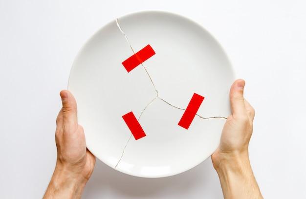 Mãos de homem segurando um prato branco quebrado, peças coladas com fita vermelha. metáfora para o divórcio, relacionamentos, amizades, crack no casamento. o amor se foi