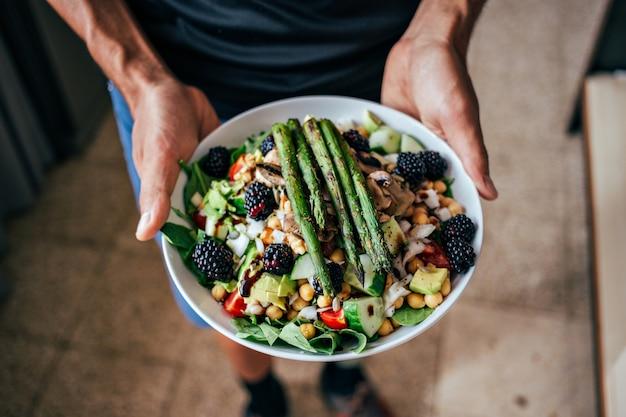 Mãos de homem segurando um prato fundo cheio de salada paleo-vegetariana saudável feita de ingredientes biológicos orgânicos frescos, vegetais e frutas, frutas vermelhas e outras coisas nutricionais