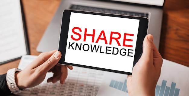 Mãos de homem segurando um tablet com texto compartilhar conhecimento no local de trabalho. empresário trabalhando na mesa com documentos