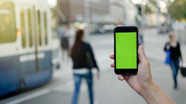 Mãos de homem segurando um telefone inteligente com tela verde.