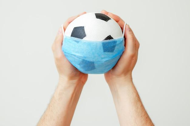 Mãos de homem segurando uma bola de futebol na máscara