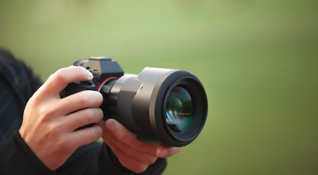 Mãos de homem segurando uma câmera tirando fotos