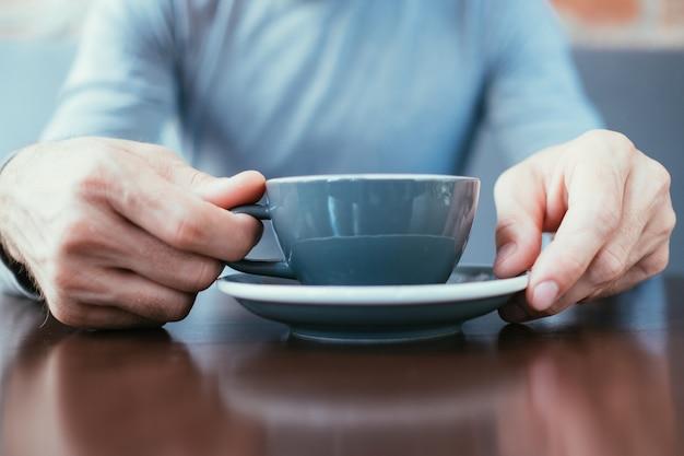 Mãos de homem segurando uma caneca. café cappuccino com leite de chocolate quente ou chá em uma xícara.