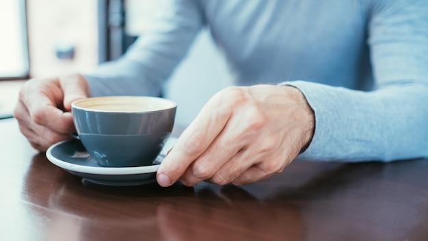 Mãos de homem segurando uma caneca de café. dependência de cafeína e maus hábitos.