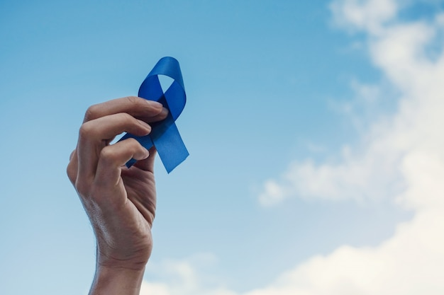 Mãos de homem segurando uma fita azul sobre o céu azul, conscientização do câncer de próstata, novembro azul