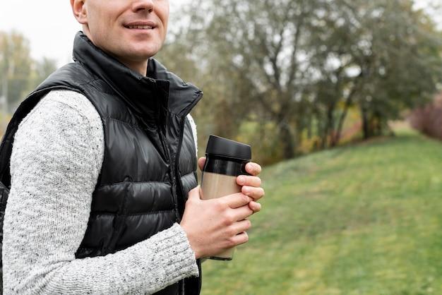 Mãos de homem segurando uma garrafa térmica na natureza