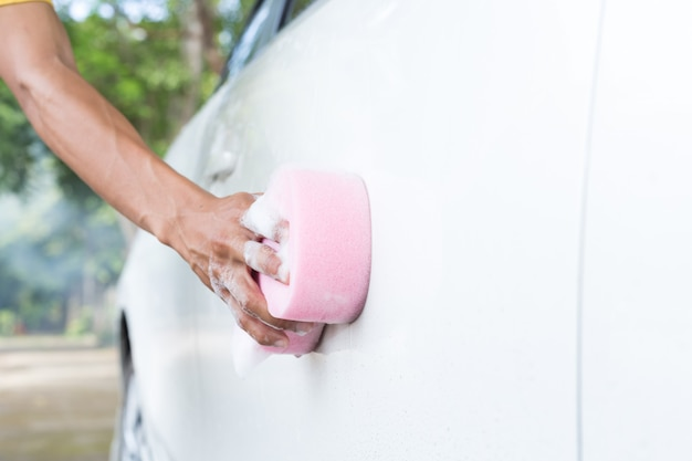 Mãos de homem segurar esponja para lavar carro branco