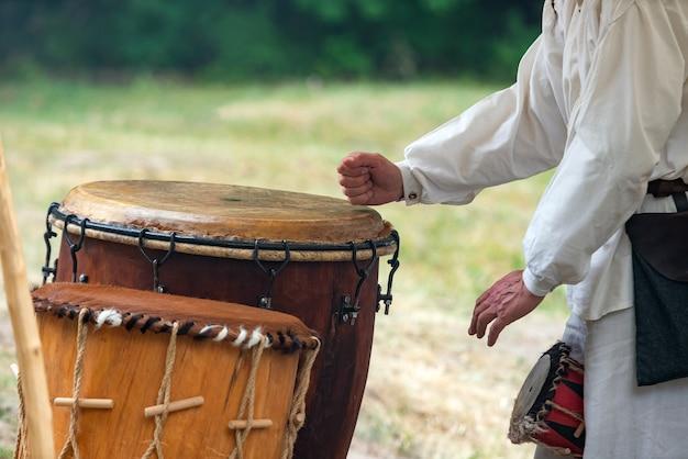 Mãos de homem tocando tambor de couro ao ar livre.
