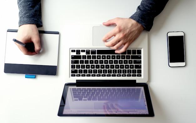 Mãos de homem trabalhando no laptop moderno e tablet gráfico
