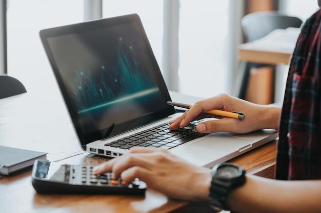 Mãos de homem usando calculadora e computador portátil