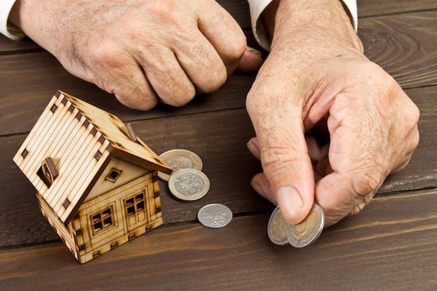 Mãos de homem velho e uma casa modelo com as moedas na mesa