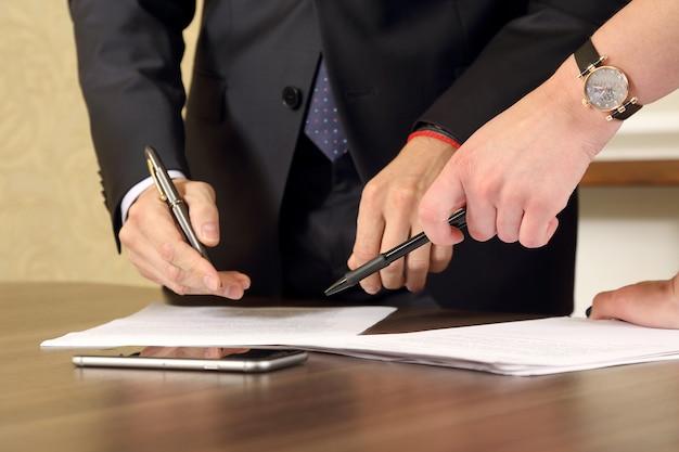 Mãos de homens e mulheres de negócios estudando os documentos