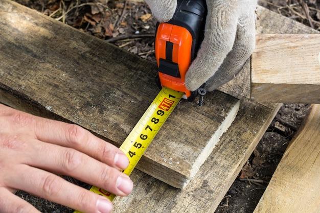 Mãos de homens, medindo uma placa de madeira com uma roleta no canteiro de obras