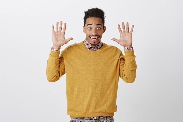 Mãos de jazz sempre na moda. retrato de jovem alegre e emotivo, com corte de cabelo afro, levantando as palmas das mãos e sorrindo amplamente, se rendendo ou expressando simpatia e bom humor