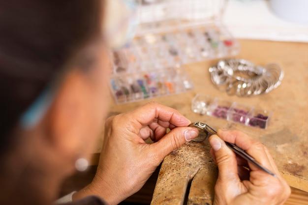 Mãos de joalheiro colocando uma joia no anel