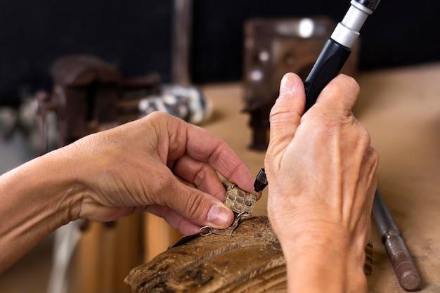 Mãos de joalheiro criando design para pulseira
