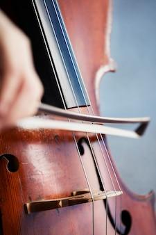 Mãos de jogador violoncelista. violoncelista tocando violoncelo no fundo do campo. arte musical, paixão pelo conceito de música. música clássica violoncelista profissional solo executar