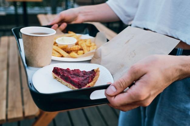 Mãos de jovem carregando a bandeja com o almoço
