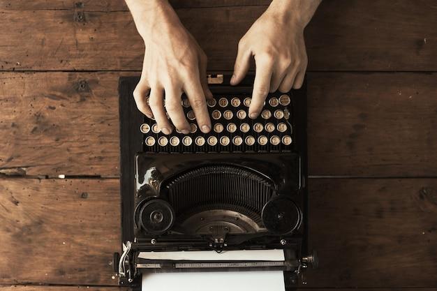 Mãos de jovem digitando em uma máquina de escrever vintage antiga