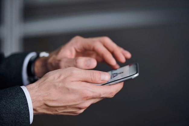 Mãos de jovem elegante em trajes formais usando smartphone para ver fotos ou publicá-las nas redes sociais
