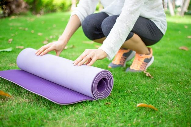 Mãos de jovem mulher que desenrolam tapete de exercícios
