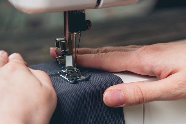 Mãos de jovem na máquina de costura