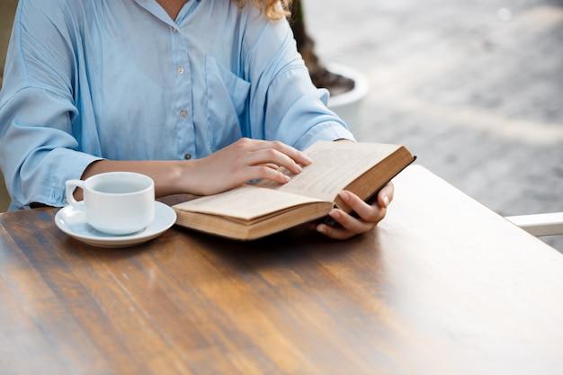 Mãos de jovem sentado à mesa com uma xícara de café e livro.