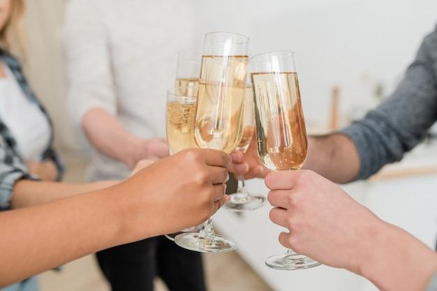 Mãos de jovens amigos multirraciais tocando taças de champanhe espumante enquanto brindam pelo ano novo ou outro feriado na festa