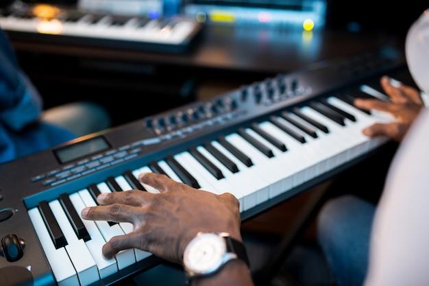 Mãos de jovens compositores ou músicos africanos tocando as teclas do piano enquanto trabalhavam em um estúdio de gravação de som